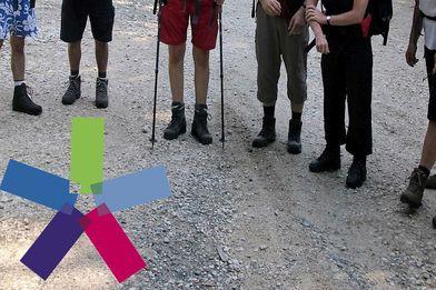 im halbkreis stehende leute mit Wanderstöcken, links unten das bunte Windrad - Copyright: Silke Meyer