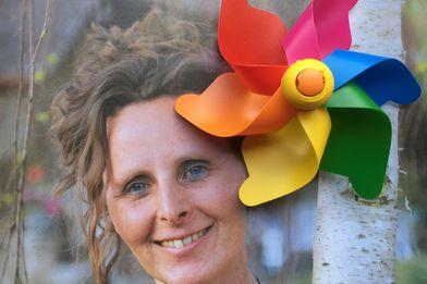 eine Frau, die sich mit der linken Seite an einem  Birkenstamm anlehnt, rechts oben das bunte Windrad - Copyright: Birke Knopp