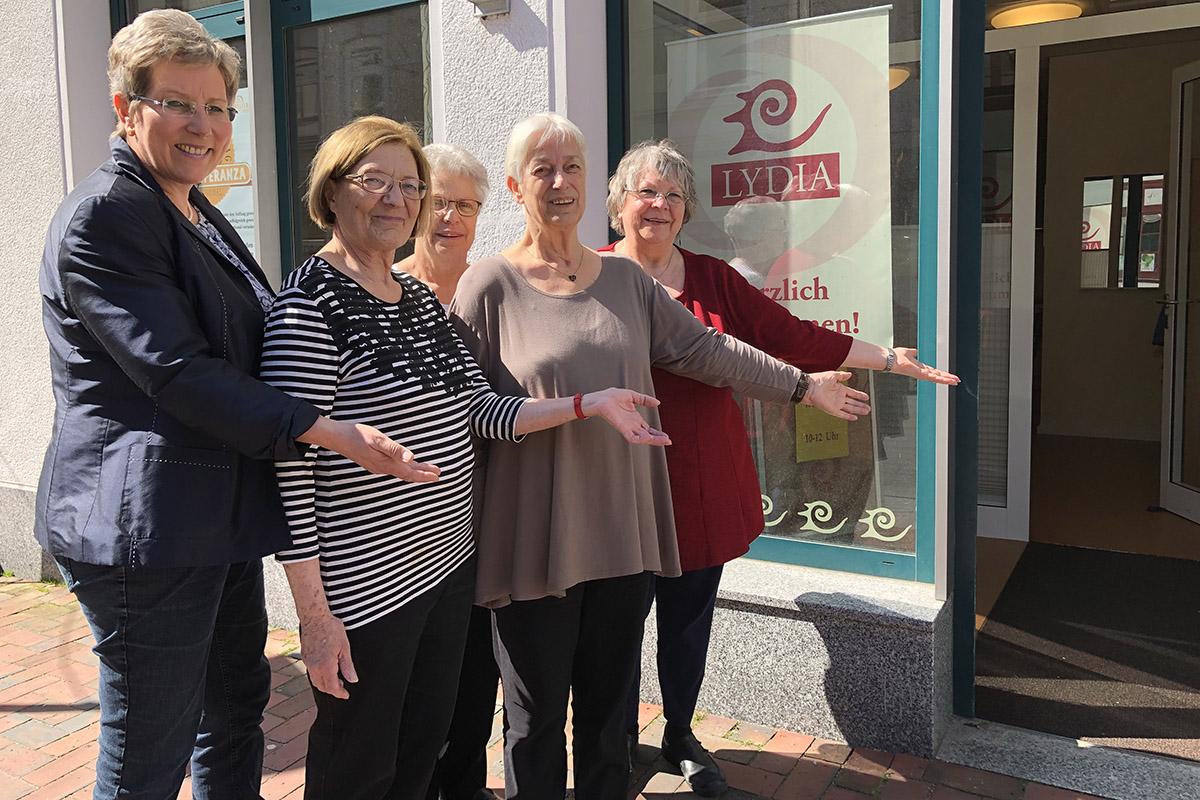 Die fünf Mitarbeiterinnen des Frauenwerkes stehen nebeneinander und zeigen mit den händen einladend auf die offene Eingangstür des Lydia Cafés